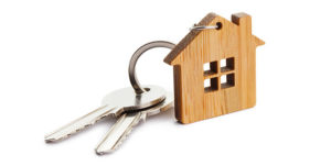 Wooden keychain in the shape of a house with two keys attached - Cripps Realty