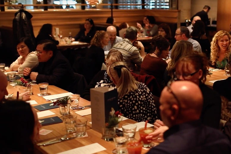 People laughing and talking at a restaurant - Cripps Realty
